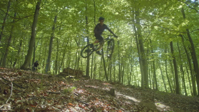 slo mo mtb bikers jumping over a wooden ramp - mountain bike stock videos & royalty-free footage