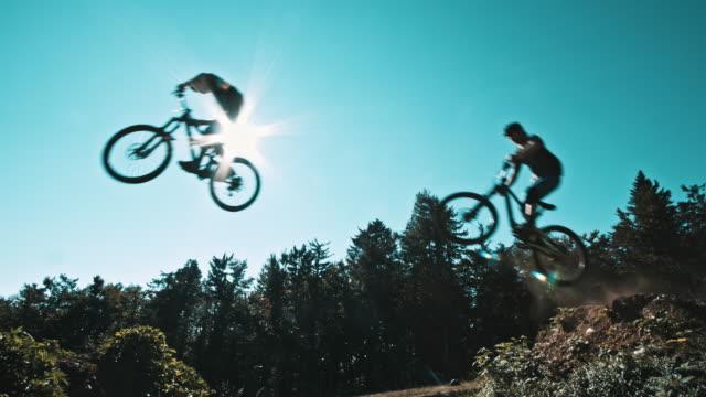 slo-mo-mtb biker über den himmel springen - mountainbike stock-videos und b-roll-filmmaterial