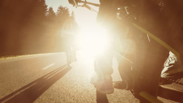 POV Biker's leg lit by sun while riding on countryside road