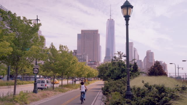 bikers on west side bike path with freedom tower in background - jackson new jersey stock videos and b-roll footage