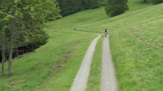 Bikers race up narrow road through green pasture and forest