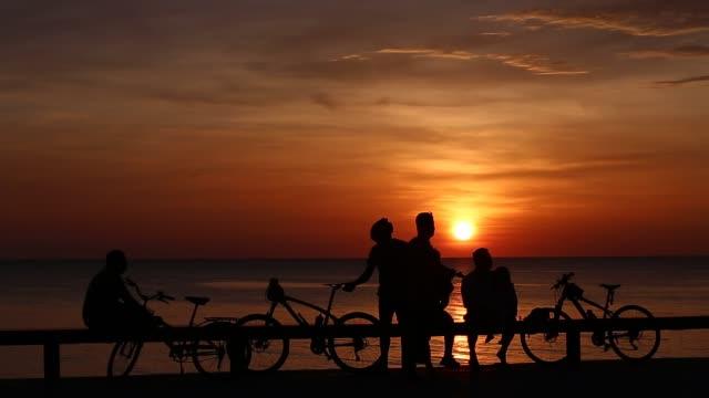 vídeos de stock, filmes e b-roll de os motociclistas relaxam com nascer do sol na praia - triatleta