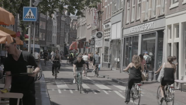 bikers ride on the street in amsterdam, wide shot - cityscape stock videos & royalty-free footage