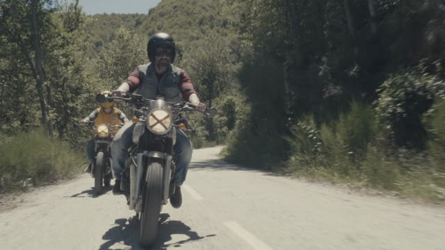 bikers riding motorcycles on a mountain road - motorradfahrer stock-videos und b-roll-filmmaterial