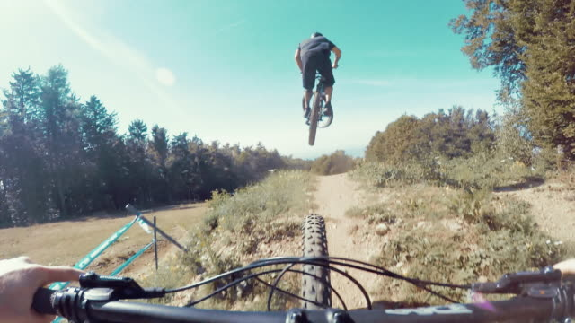 pov bikers riding on a downhill trail - mountain bike stock videos and b-roll footage