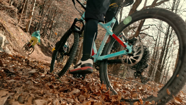 slo mo bikers riding their mountain bikes down a forest trail in fall - mountain bike stock videos & royalty-free footage