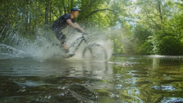 vidéos et rushes de slo mo mtb motards à cheval à travers un ruisseau - jeunes hommes