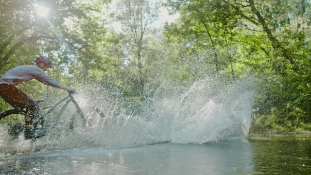 super slo mo mtb bikers riding through a stream - bicycle trail outdoor sports stock videos & royalty-free footage