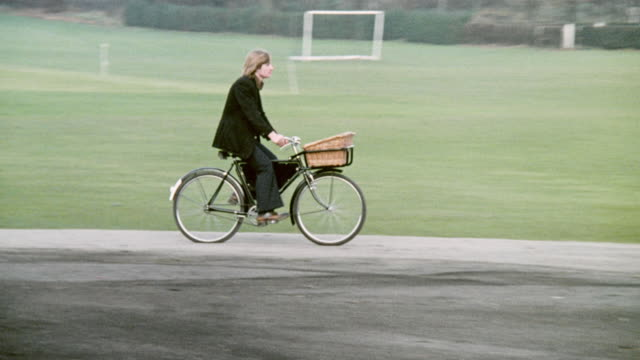 1974 montage bikers riding various old time bicycles and two-wheelers around a park / united kingdom - 1974 bildbanksvideor och videomaterial från bakom kulisserna