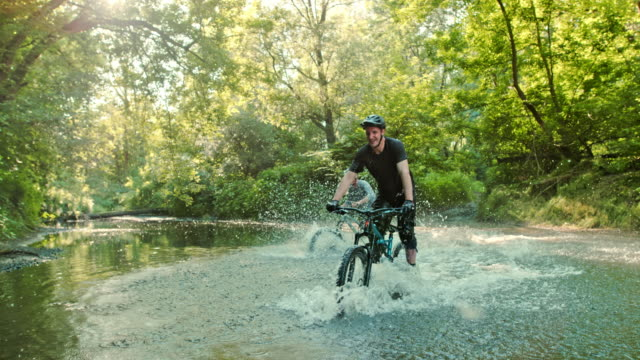super slo mo mtb bikers splashing through a stream - bicycle trail outdoor sports stock videos & royalty-free footage