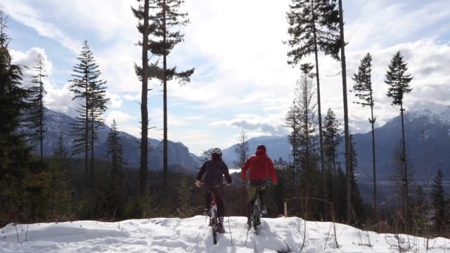 vídeos y material grabado en eventos de stock de ciclistas atraviesan nieve profunda a la vista de la montaña - capucha