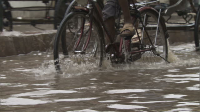Bikes pedalled through flood water, Varanasi Available in HD.