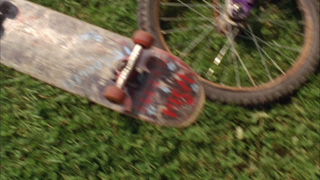oh cu pan bikes, skateboards, backpack and sandals lying on grass / cazenovia, new york, usa - medium group of objects stock videos & royalty-free footage