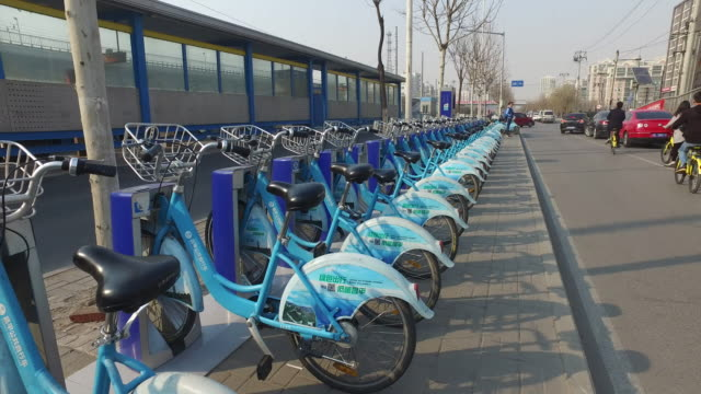 bikesharing is the latest trend in public transportation in china's major cities the bikes can be locked and unlocked anywhere via a smartphone app... - sharing stock videos & royalty-free footage