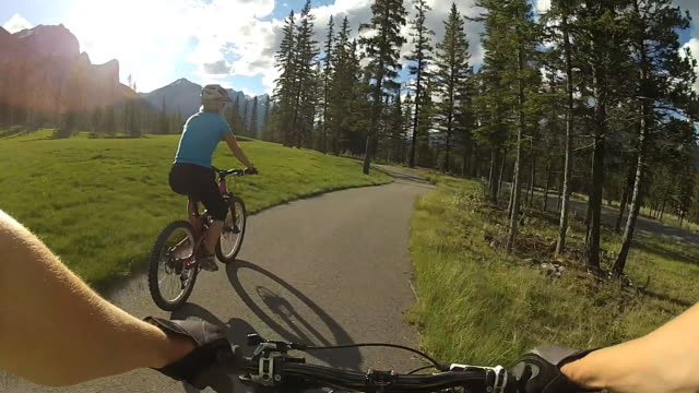 POV biking behind a middle aged woman on paved mountain pathway