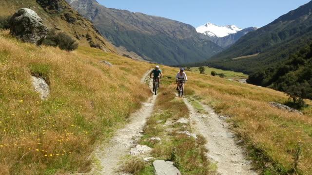 biking couple follow dirt track through mountain meadow - fahrzeug fahren stock-videos und b-roll-filmmaterial