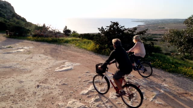 stockvideo's en b-roll-footage met biking couple follow pathway above pines, sea - repubiek cyprus