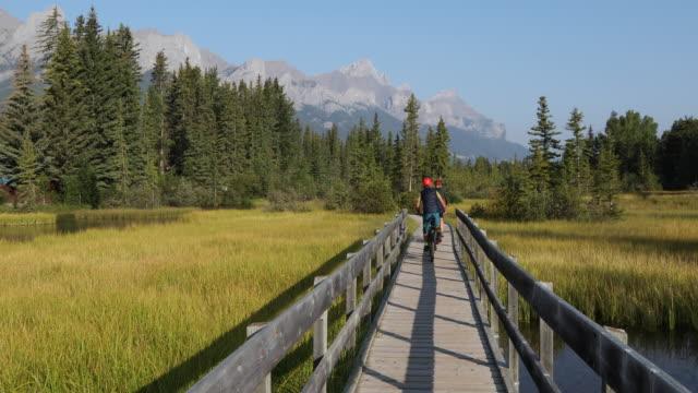 Biking couple follow wooden boardwalk over marsh, mountains
