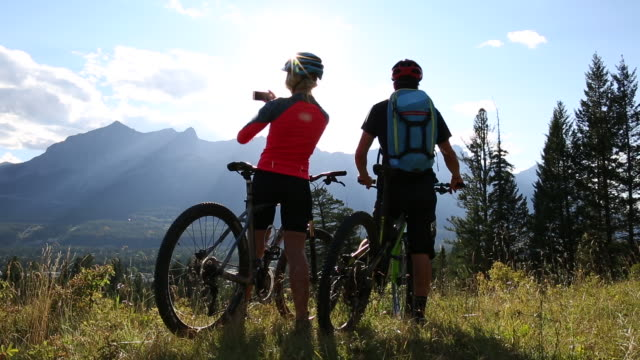 biking couple pause in mountain meadow, take smart phone pic - resting stock videos & royalty-free footage