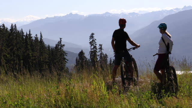 biking couple reach high grass promontory, look off to view - british columbia stock videos & royalty-free footage