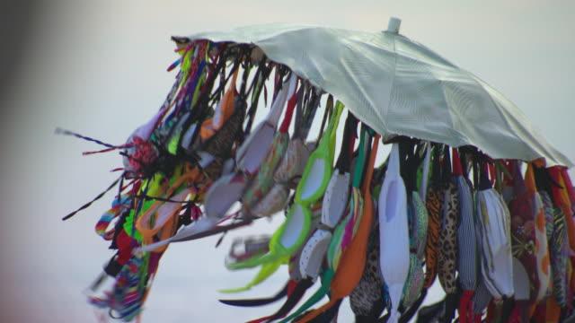 Bikini sellers hawking their wares bikinis displayed under beach umbrella bobbing above people's heads