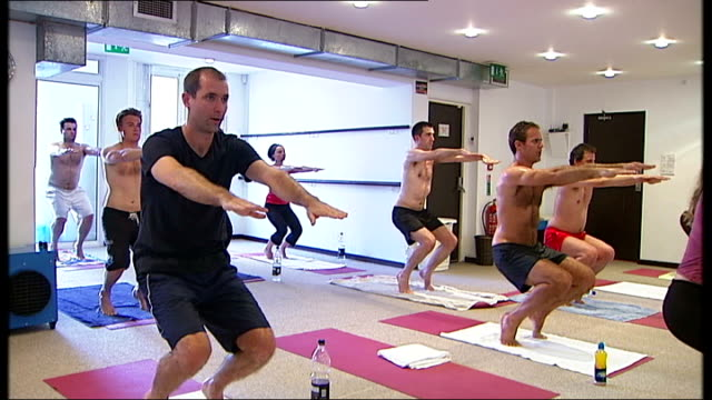 bikram yoga class reporter clarke struggling with class/ more of class holding yoga positions - struggle stock videos and b-roll footage