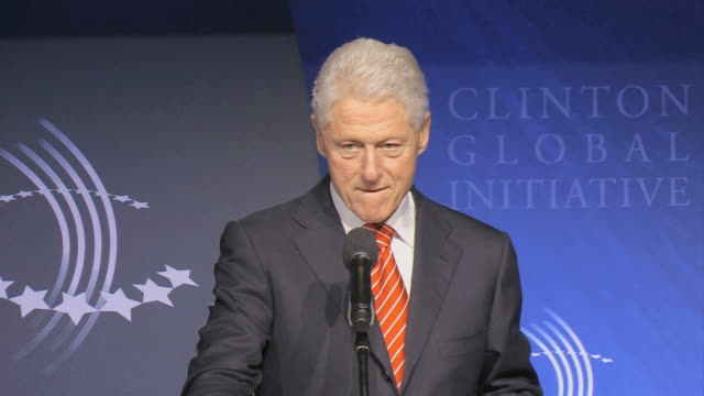 bill clinton removing spectacles while speaking into microphone at podium shaking hands / new york city new york usa / audio - pult stock-videos und b-roll-filmmaterial