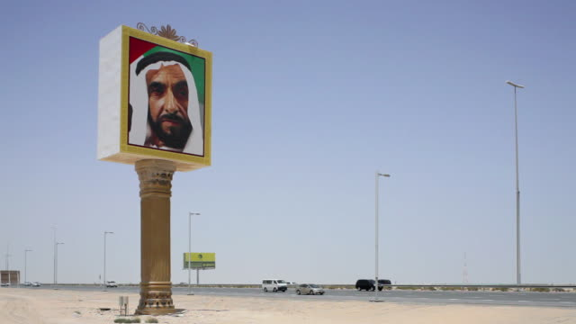 WS Billboard of Sheikh Zayed in desert, traffic on road in background / Dubai, United Arab Emirates