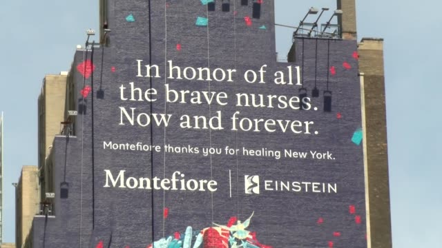 billboard on facade of building on 34th street in manhattan. zoom out to show face of nurse. - 34th street stock videos & royalty-free footage