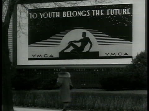 ymca billboard 'to youth belongs the future' man studying at desk man talking at dinner table ext couple man w/ pipe woman in shades talking people... - 1940 stock videos & royalty-free footage