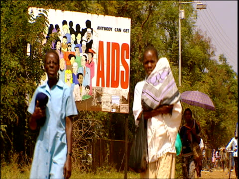 vidéos et rushes de billboard warning about aids people walking towards and past camera - panneau commercial