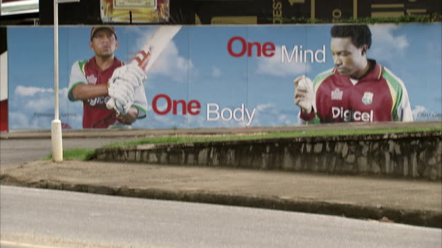 Billboards line a busy street. Available in HD.