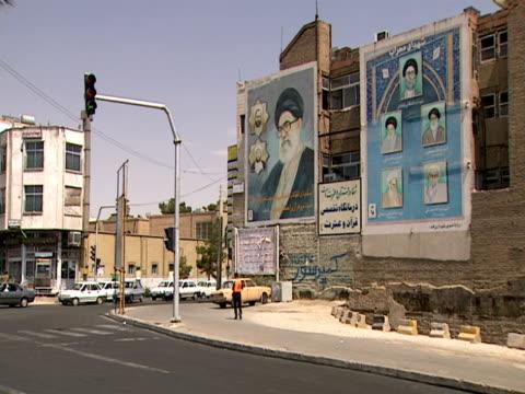 montage billboards on the side of buildings displaying images of ali khamenei, supreme leader of iran / qom, iran - 中東点の映像素材/bロール