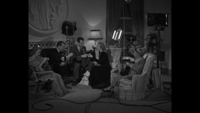 Billie Burke Madeleine Carroll Dame May Whitty sit in arm chairs on set knitting / costars Fred MacMurray John Loder enter and sit in front of...