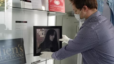 """stockvideo's en b-roll-footage met billie eilish, daniel craig, and finneas signed """"no time to die"""" single cover lithograph is displayed at musicares charity relief auction press... - litho"""