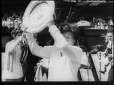 billie jean king holding up trophy after winning wimbledon / england / newsreel - ビリー・ジーン・キング点の映像素材/bロール