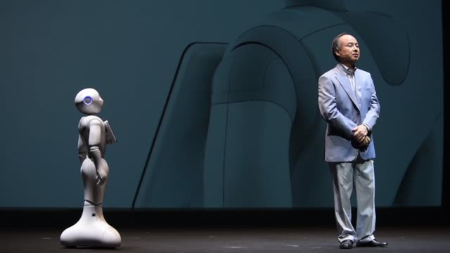 ws billionaire masayoshi son chairman and chief executive officer of softbank corp puts his hand on robot pepper ms robot pepper is demonstrated... - 記者会見点の映像素材/bロール