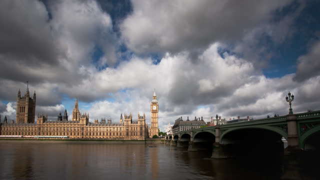 billowing clouds flow over the houses of parliament in london. - westminster bridge stock videos and b-roll footage