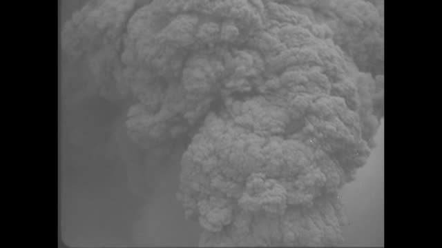billowing clouds of ash as the volcano erupts / aerial large crater with whiffs of smoke [note film has nitrate deterioration] - 1944 stock videos & royalty-free footage