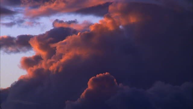 Billowing purple and orange storm clouds turn the sky dark, Maui Available in HD.