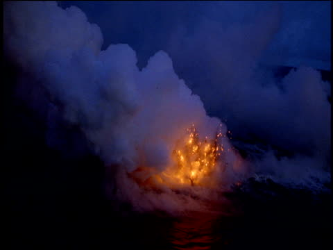 Billowing smoke emerges from surface of sea followed by spewing molten lava from underwater volcano