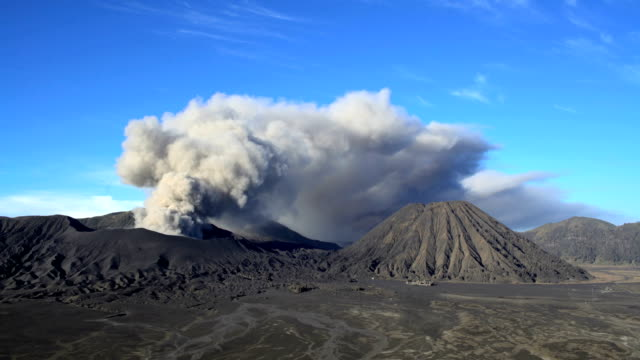 billowing smoke erupting from mount bromo volcano java - erupting stock videos & royalty-free footage