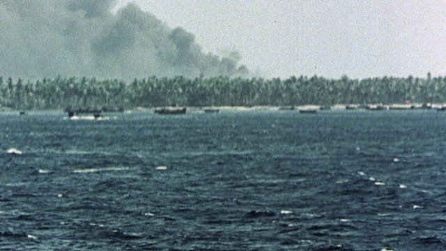 vídeos de stock, filmes e b-roll de billows of dark smoke rising from tropical island during naval bombardment / makin gilbert islands - guerra do pacífico