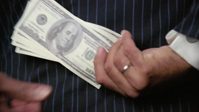 us$100 bills exchanging hands behind man's back - bribing stock videos & royalty-free footage