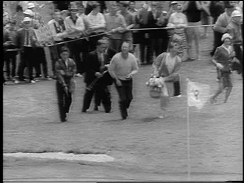 billy casper + caddies walking towards 18th hole at u.s. open / newsreel - bandierina da golf video stock e b–roll