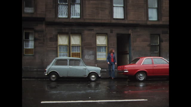 billy connolly exits a brown residential building, passes between two parked cars, crosses a road and enters his former school. - britische kultur stock-videos und b-roll-filmmaterial