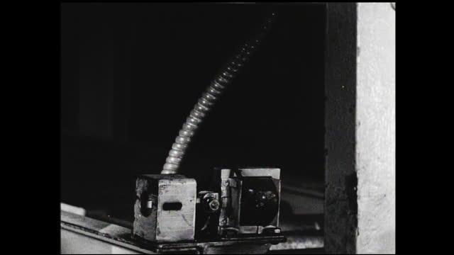 bin on conveyor belt traveling toward the camera and is stopped by small device; close up on the device - 1940 1949 bildbanksvideor och videomaterial från bakom kulisserna