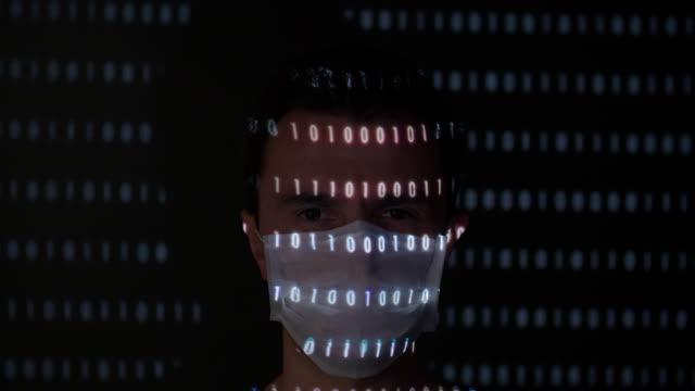 proiezione binaria dei dati sul viso di un uomo che indossa una maschera chirurgica - projection video stock e b–roll