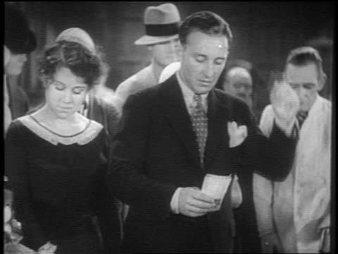vídeos de stock e filmes b-roll de bing crosby having argument with woman as group in background looks on / he starts singing / short - 1931
