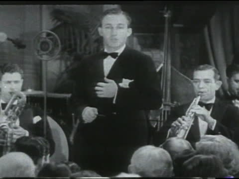 """stockvideo's en b-roll-footage met bing crosby singing """"i surrender dear"""" with adult caucasian male musicians playing behind him; adult caucasian men and women slow dancing in fg.... - bing crosby"""